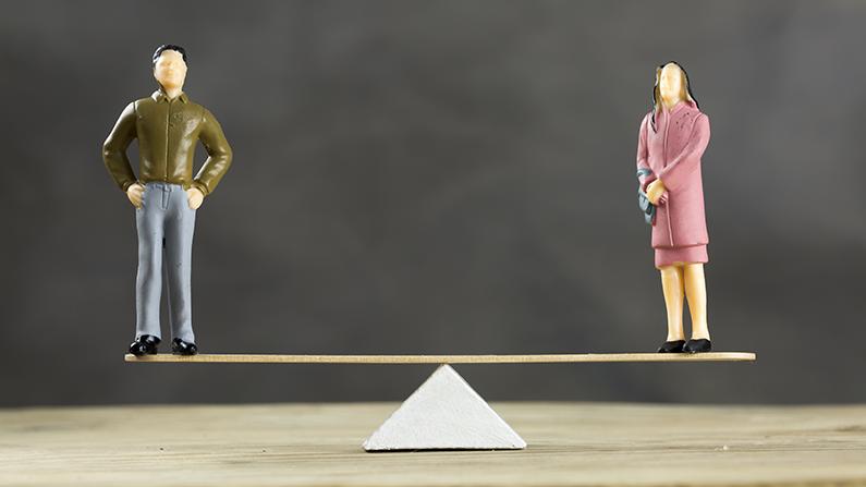 En manlig respektive en kvinnlig docka på varsin ände av en gungbräda i jämvikt.